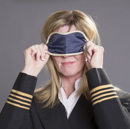 personal grooming: Sleepy aircrew officer using an eye shade Stock Photo