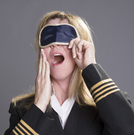 personal grooming: Sleepy aircrew officer yawning and using an eye shade
