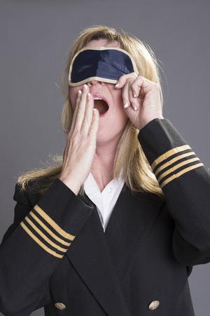 aircrew: Sleepy aircrew officer yawning and using an eye shade