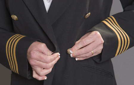 personal grooming: Airline officer fastening button on her uniform