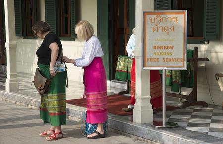 the entering: Tourists borrow a sarong before entering a religious temple Thailand