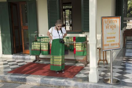sarong: Tourist borrows a sarong before entering a religious temple Thailand Stock Photo