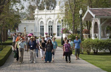 guia turistico: La guía turística con un grupo de visitantes en Bang Pa en Palacio Ayutthaya en Tailandia
