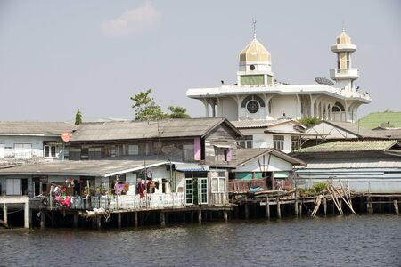 waterfront property: Overlooking the Chao Phraya river a Mosque and riverfront homes Bangkok Thailand Stock Photo
