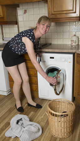 emptying: Woman using a washer dryer machine Stock Photo