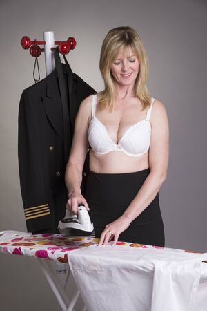 airline pilot: Pilot ironing her uniform shirt