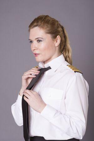 airline pilot: Airline pilot tying her necktie