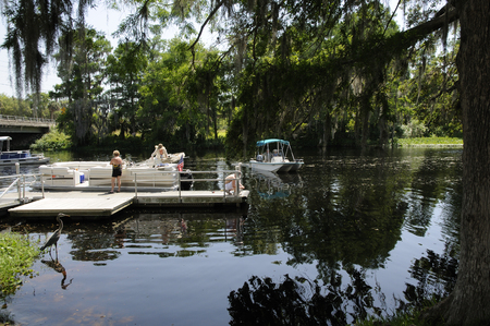 manoeuvre: A pontoon motorboat and dayboat on the Rainbow River at Dunnellon Marion County Florida USA Editorial