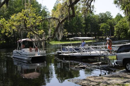manoeuvre: Bringing a Pontoon boat ashore from the Rainbow River at Dunnellon in Marion County Florida USA