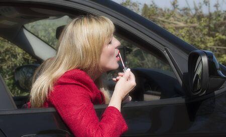 motorist: Female motorist applying lip gloss using driving mirror