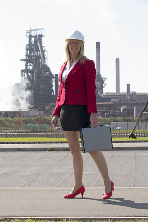 smartly: Businesswoman wearing a hard hat in an industrial environment