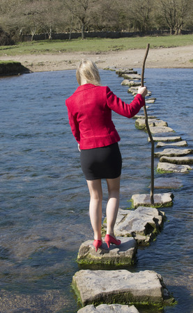 transcend: Stepping stones woman crossing river using a tree branch for balance