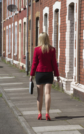 residential street: Businesswoman carrying briefcase along a residential street