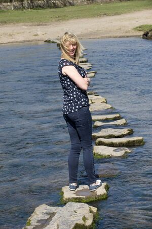 stepping on: Woman in barefeet crossing a river using stepping stones Stock Photo