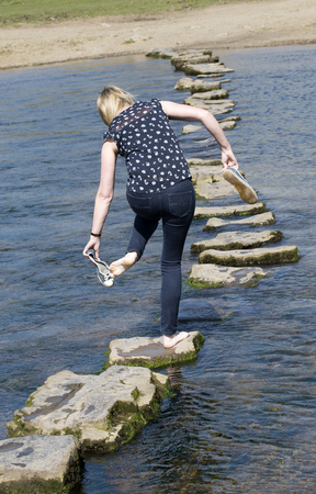 Woman in barefeet crossing a river using stepping stones Stock Photo