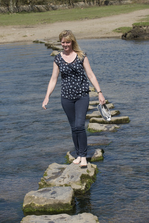 Woman in barefeet crossing a river using stepping stones Archivio Fotografico