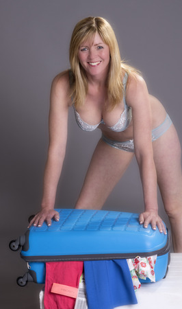 suitcase packing: Woman closing holiday suitcase