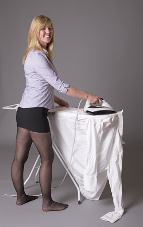 ironing board: Woman standing at ironing board