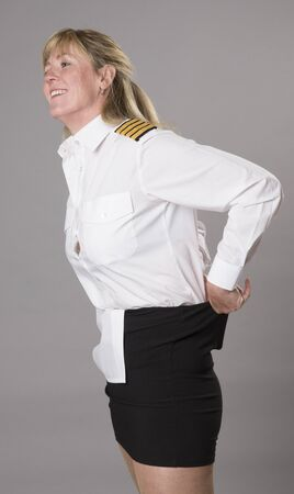 Woman airline officer tucking uniform shirt into her skirt