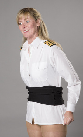 Woman airline officer tucking uniform shirt into her skirt