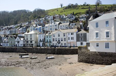 waterfront property: River Dart at low tide overlooked by colourful properties at Dartmouth Devon UK Editorial