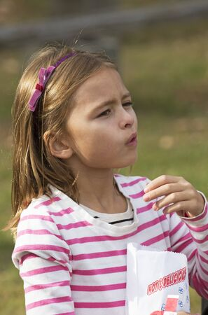 mouthful: Young girl eating popcorn from a paper bag