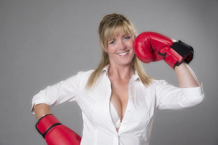 revealing: Female boxer wearing a revealing shirt and red boxing gloves taking a punch on the chin Stock Photo