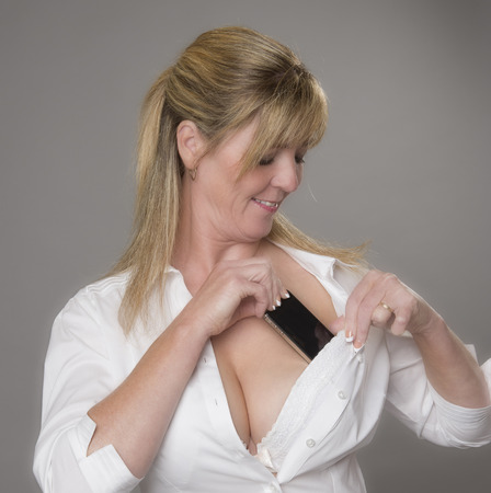 concealment: Woman tucking her mobile phone into her white bra for safety