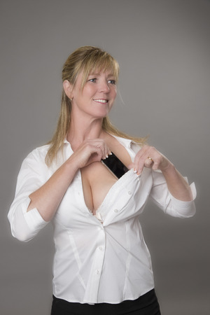 Woman tucking her mobile phone into her white bra for safety