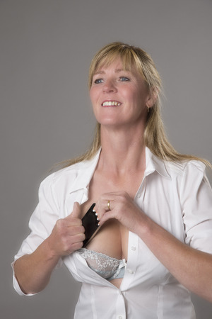Woman putting mobile phone into her bra for safe keeping Stock Photo