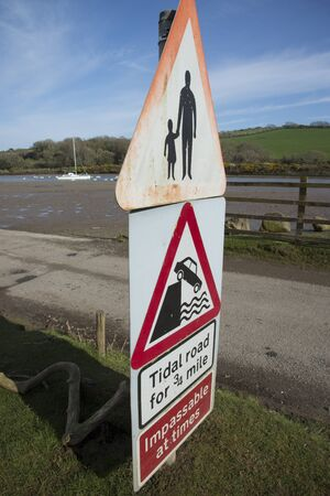 notices: Tidal road warning notices at Aveton Gifford Devon England Uk