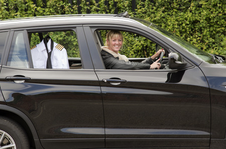 people travelling: Woman driving to work with her uniform on a hanger in the car window