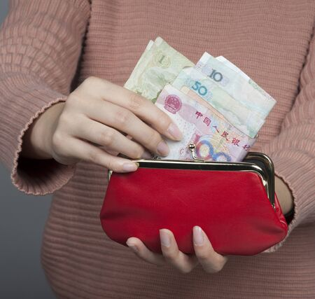 the mainland: Chinese woman holding Yuan banknotes the official currency of mainland China with a red purse Stock Photo