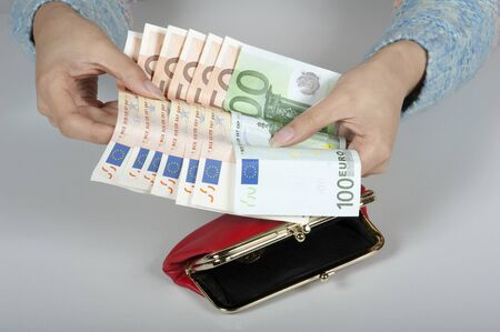 monies: High denomination Euro banknotes in a womans hand which is holding a red leather purse Stock Photo
