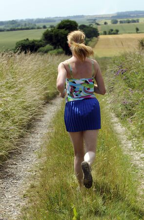 keep fit: Woman running to keep fit and healthy in the English countryside