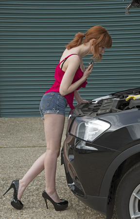 telephoning: Young woman driver holding a mobile phone and looking into the bonnet of her car