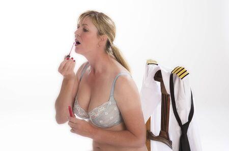 gloss: Female airline pilot applying lip gloss to her face