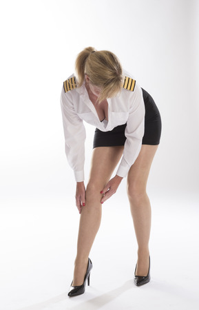 bending forward: Attractive female airline pilot checking her tights prior to going on duty