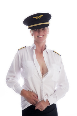 Attractive female airline pilot tucking shirt into skirt