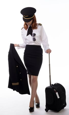 Airline First officer in uniform carrying jacket and holding carry on flight bag Archivio Fotografico