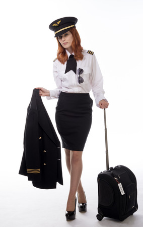 smartly: Airline First officer in uniform carrying jacket and holding carry on flight bag Stock Photo