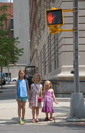 hand signal: Young children waiting to cross the street standing by red hand signal Stock Photo