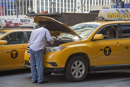 yellow cab: New York yellow cab driver inspecting his brokendown vehicle NYC Editorial
