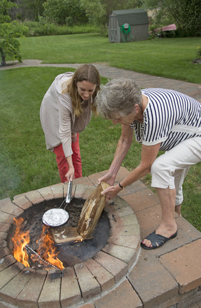 fire pit: Women cooking a pan of popcorn in a foil covered pan over a garden fire pit