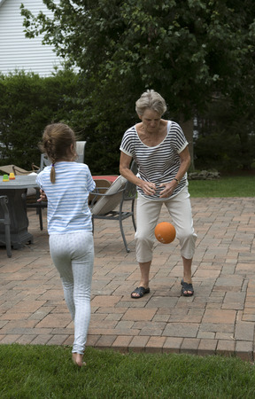 oap: Elderly woman playing ball with a young child