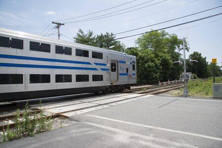 long island: MTA Long Island Railroad train passing a level crossing at Mattituck USA Editorial