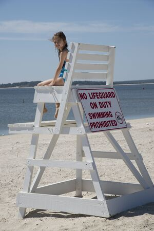 not painted: Young girl climbing on a Lifeguard chair on Jamesport Beach Long Island USA