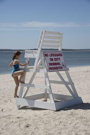 not painted: Young girl climbing on a Lifeguard chair on Jamesport Beach, Long Island, USA Stock Photo