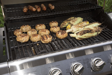 barbecues: Food cooking on a gas barbecue. Sausages,turkey burgers and corn
