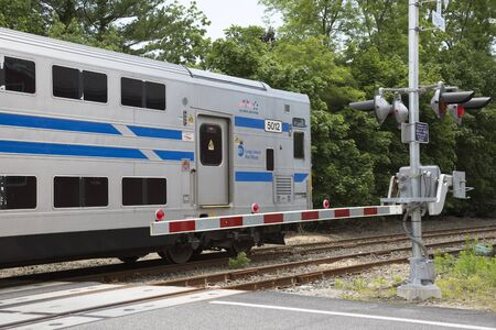 long island: MTA Long Island Railroad train passing a level crossing at Mattituck, USA Editorial